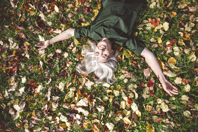 Mature woman smiling while lying on grass at park