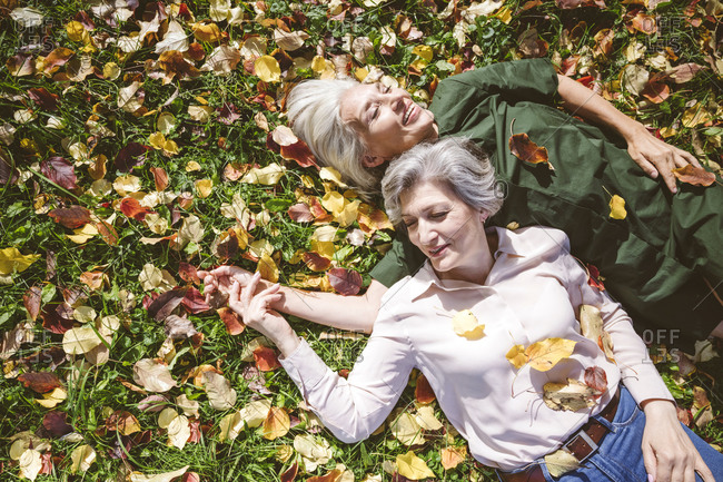 Happy women smiling while lying on grass at public park