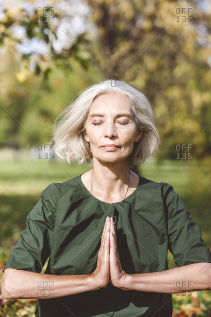 Woman sitting with hands clasped while doing yoga at park