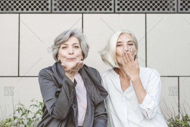 Businesswoman blowing kiss while sitting against building