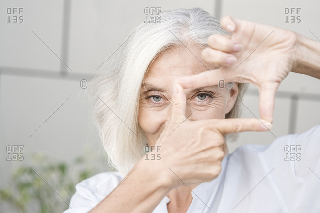 Businesswoman looking through finger frame against wall
