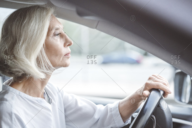 Mature businesswoman with short white hair driving car in city