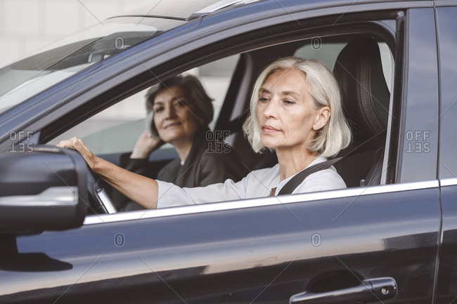 Businesswoman sitting with colleague driving car in city