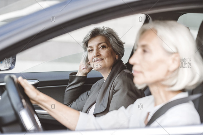 Businesswoman smiling while sitting by female colleague driving car in city