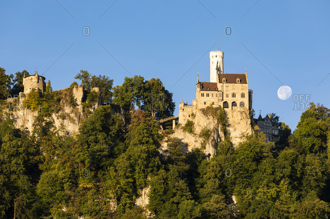 Germany- Baden-Wurttemberg- Lichtenstein Castle at dusk with moon rising in background