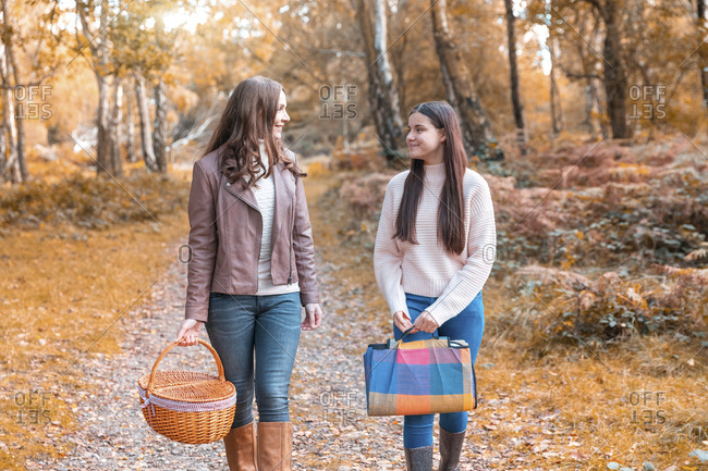Mother and daughter looking at each other while walking in Cannock Chase park during autumn