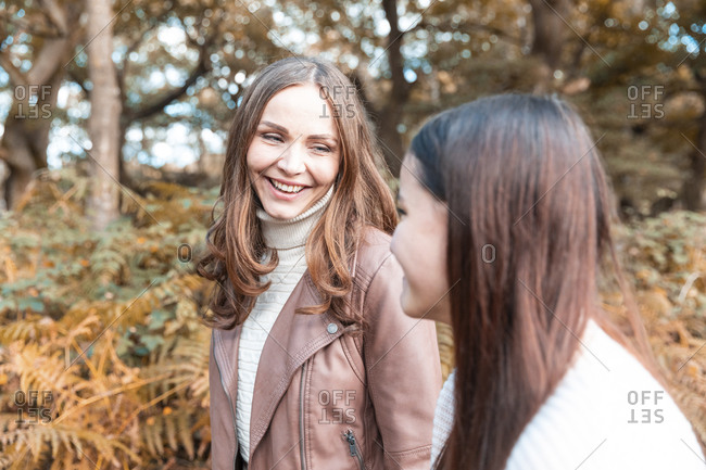 Mother and daughter smiling while walking in Cannock Chase park during autumn