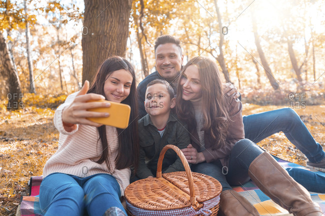 Happy family taking selfie on smart phone while sitting in park during autumn