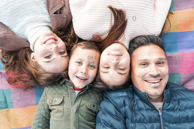 Directly above view of smiling family lying down on picnic blanket in park