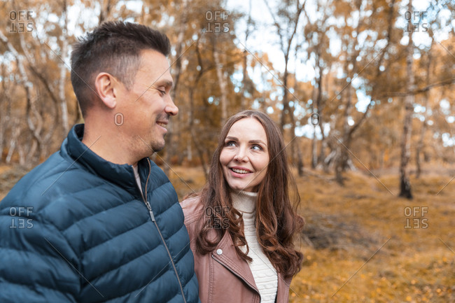 Smiling couple looking at each other while standing in park during autumn