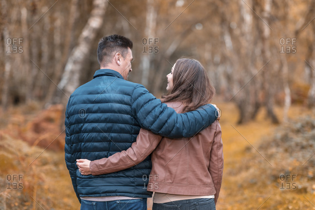 Heterosexual couple with arms around standing in Cannock Chase park during autumn