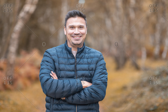 Smiling man with arms crossed standing in Cannock Chase park during autumn