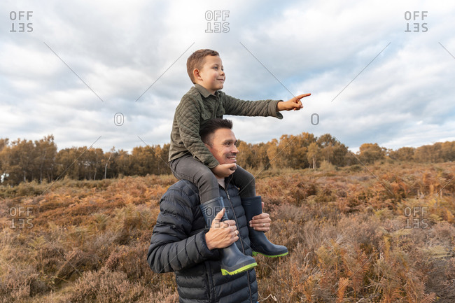 Father carrying son on shoulder standing in Cannock Chase park against cloudy sky during autumn