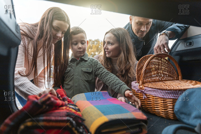 Family picking up picnic stuff from car trunk
