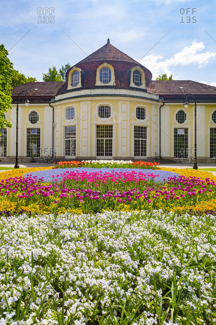 Germany- Bavaria- Bad Reichenhall- Colorful flowerbed in Royal Spa Garden with concert hall rotunda in background