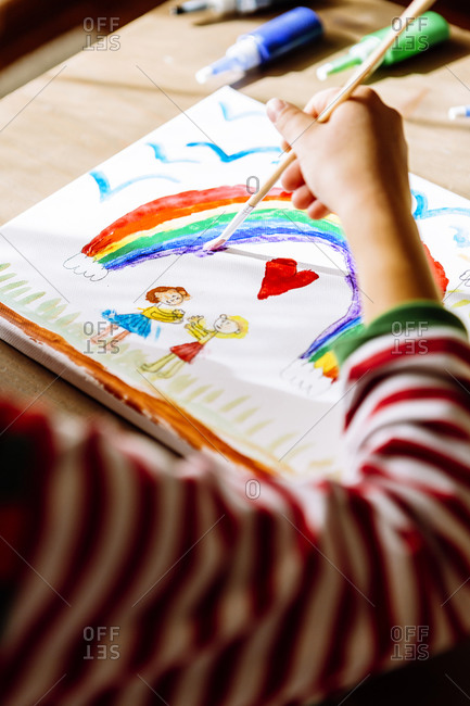 Hand of girl painting rainbow over table at home