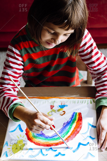 Girl painting rainbow over table at home