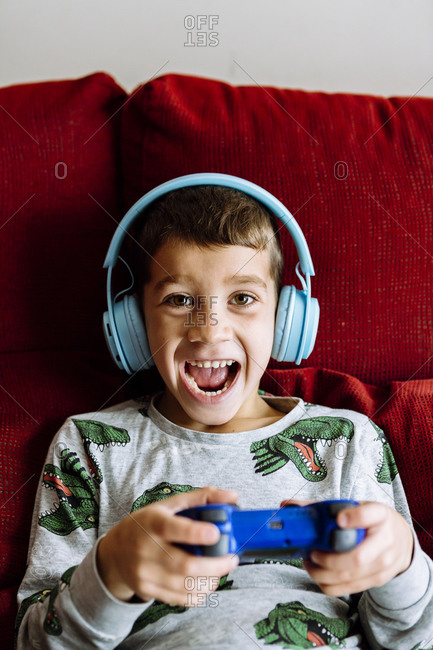 Happy boy wearing headphones while playing video game on sofa at home