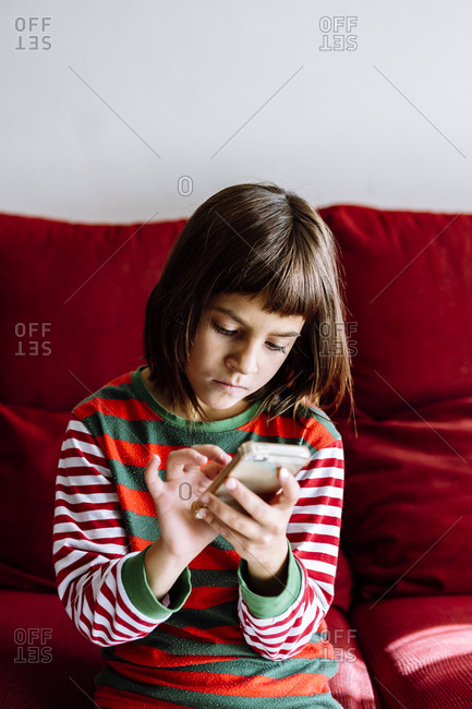 Girl using smart phone while sitting on sofa in living room