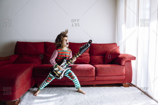 Happy girl playing guitar against sofa in living room