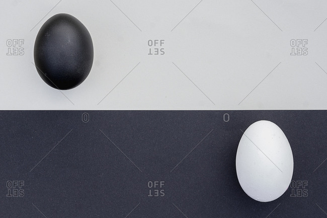 Studio shot of black and white eggs on contrasting backgrounds