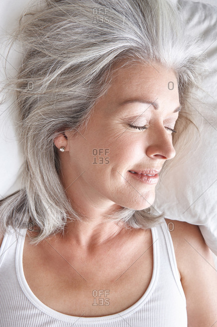 Mature attractive Caucasian woman sleeping on white sheets, head and shoulders