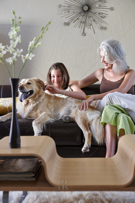 Mature woman and a teenager, mother and daughter on sofa with their golden retriever dog