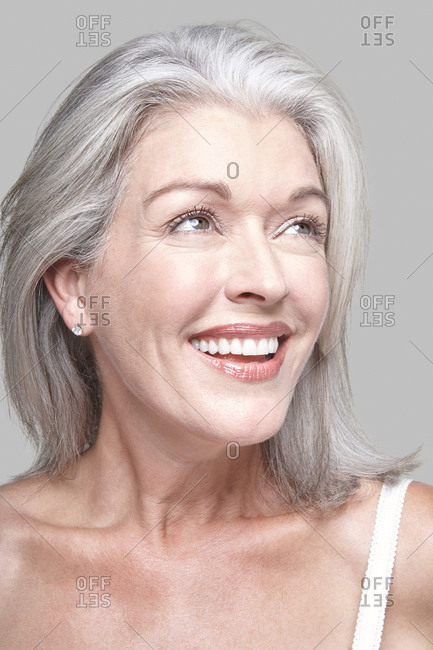 Attractive mature Caucasian woman with silver grey hair in a white tank top, bare shoulders.