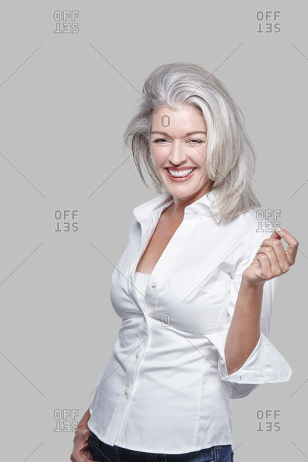 Portrait, attractive vivacious mature Caucasian woman with silver hair, laughing.