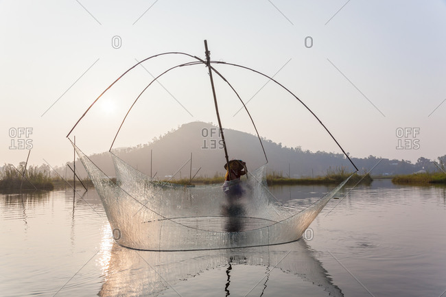 January 8, 2021: Fisherman on his boat moving arched swing nets above the water at Loktak Lake, Moirang, India