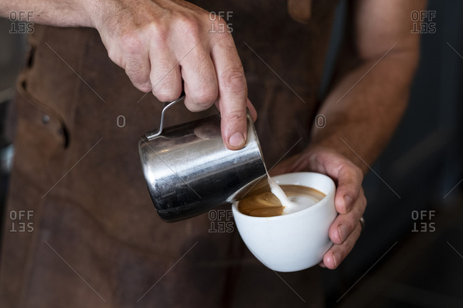 Close up of barista wearing brown apron pouring cappuccino.