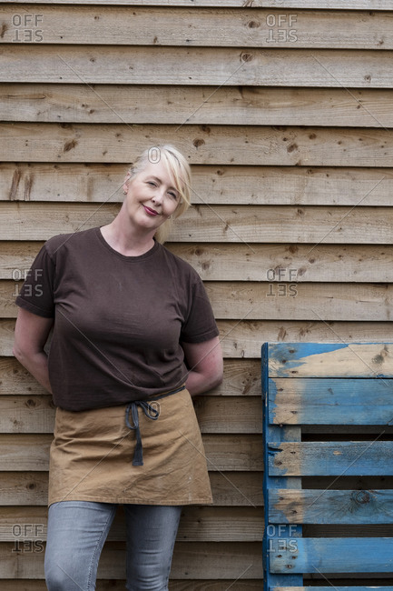 Portrait of waitress wearing brown apron, leaning against wall, smiling.