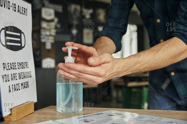 Man using hand sanitizer gel in restaurant