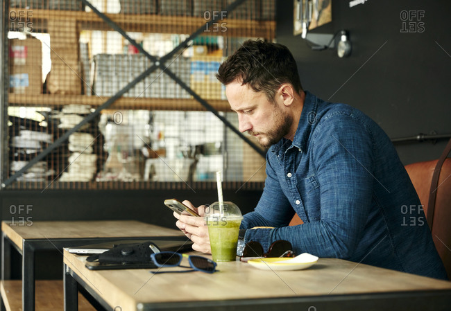 Man sitting alone at table with laptop and juice drink in cafe using smart phone