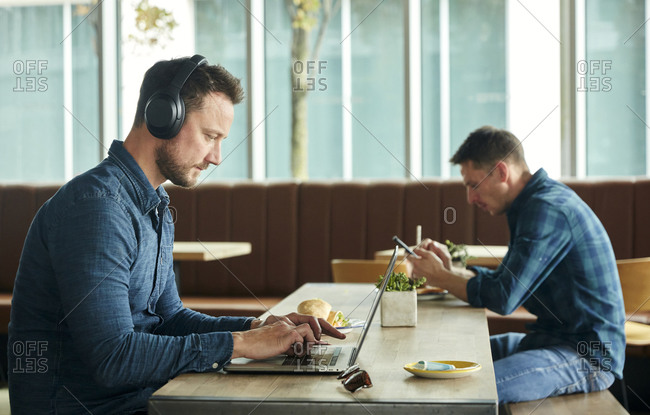 Two men seated in a cafe, working remotely  using a  laptop and smart phone