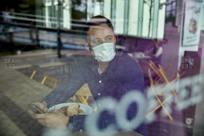 Man in a face mask seated at a cafe table, view through a window