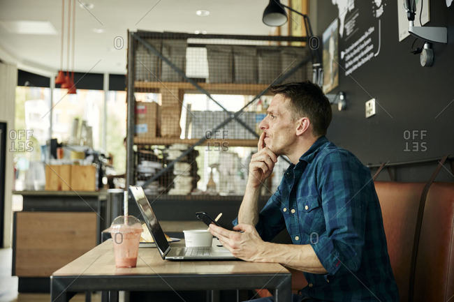 Man seated in a cafe using a laptop, wearing headphones, taking an online call.