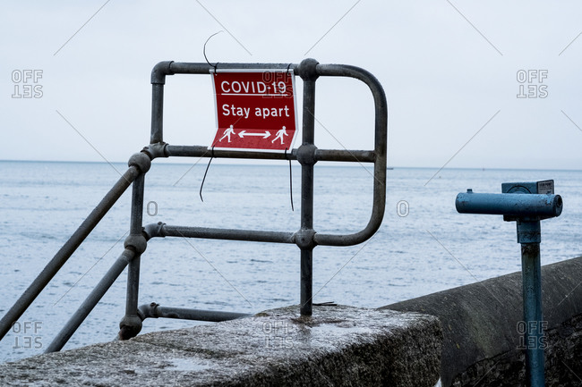Red and white Covid-19 distancing sign on a harbor wall railing.