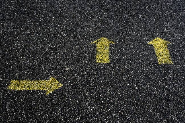 High angle close up of yellow arrow symbols painted on asphalt ground.