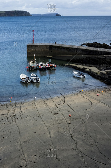 January 8, 2021: High angle view of fishing boats moored in harbor at low tide, Cornwall, UK.