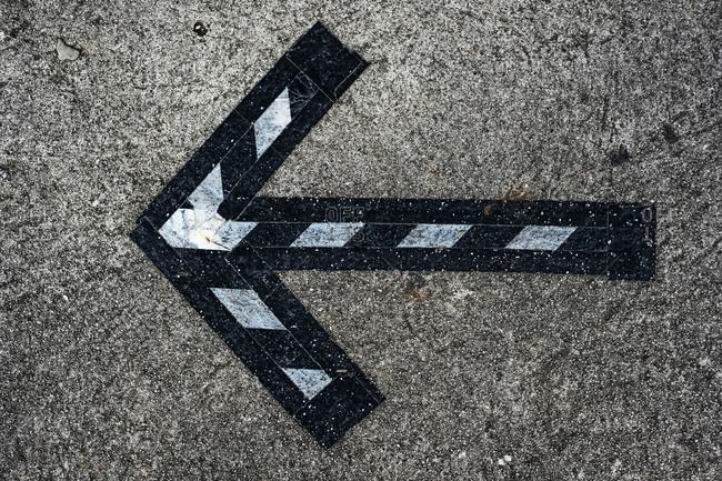 High angle close up of black and white arrow symbol on asphalt ground.