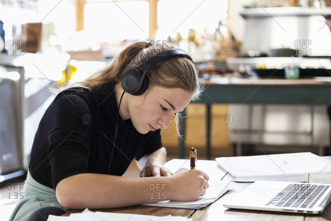 Teenage girl wearing headphones using a laptop and writing in a notebook