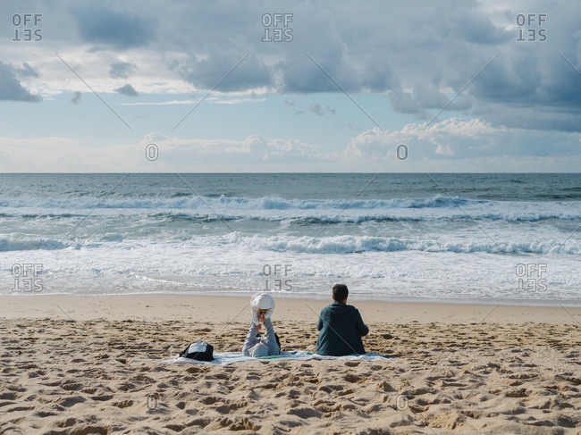 Mother playing with her child lying on the sand while the dad stares at the sea