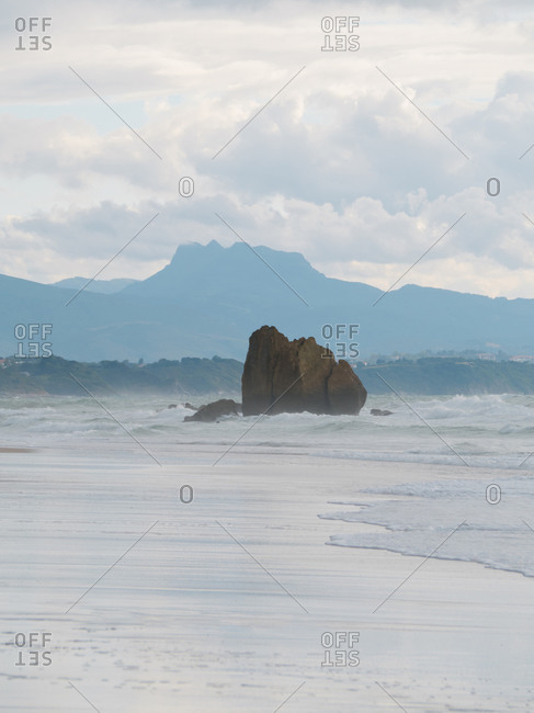 Big rock on the shore of Ilbarritz Beach during a stormy day in the south of France