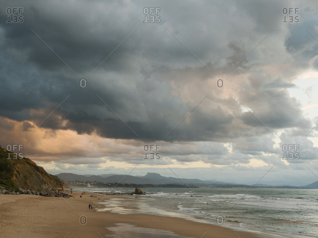 Almost empty beach in Biarritz with dark and epic sky in background