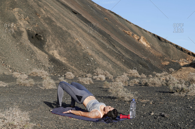 Fit young woman in sportswear doing hip thrusts during an outdoor workout in arid countryside