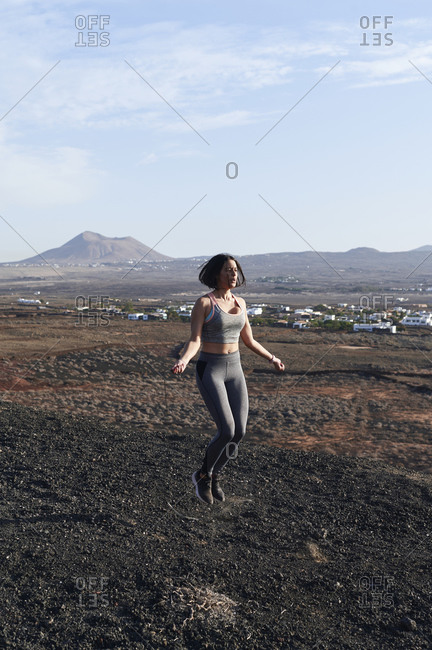 Fit young woman in sportswear jumping rope during an outdoor workout in some rocky countryside in summer