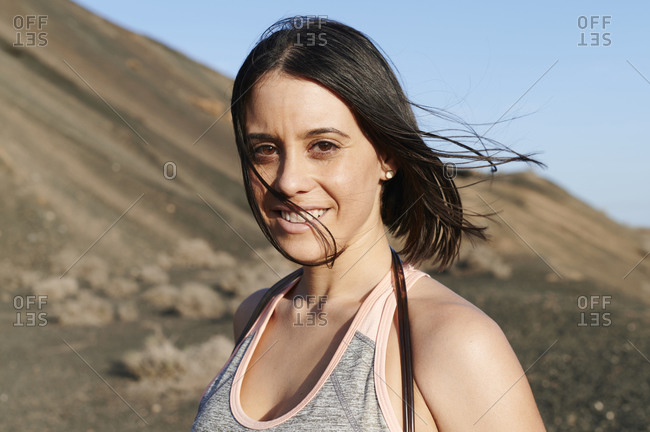 Smiling young woman in sportswear standing outside in some rocky terrain before a workout session