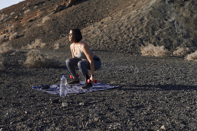 Fit young woman in sportswear doing squats with dumbbells during an outdoor workout in some rocky countryside in summer