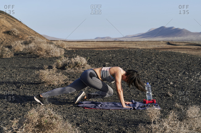 Fit young woman in sportswear doing plank crunches during an outdoor workout in arid countryside in summer